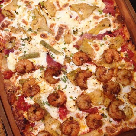 Homemade pizza: half shrimp, half ham and artichoke.